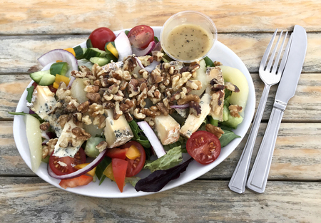 Stilton, pear and walnut salad with dressing on rustic wood background with a knife and fork