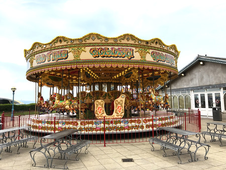 Weymouth, Dorset, United Kingdom. 19th July 2017. Old fashioned merry go round on the esplanade promenade with metal seating in the foreground.