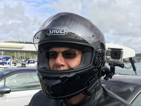 Dartmouth, Devon, United Kingdom. 27th July 2017. Motorbike rider wearing a Go Pro Hero 4 black action video camera with bluetooth communication device on his helmet. Useful for recording traffic incidents and rider action view.