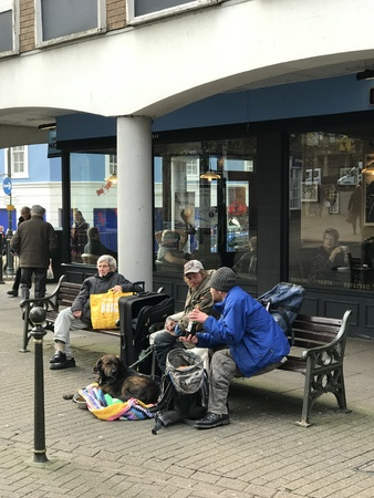 Carmarthen, Carmarthen-shire. United Kingdom. 17th November 2017. Two homeless men sitting on a bench in the town drinking a bottle of alcohol with a pet dog and belongings in a rucksack and case.