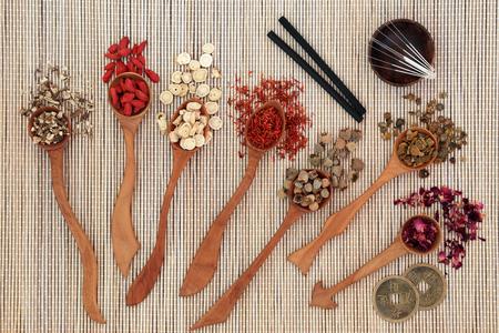 La medicina herbaria china con las hierbas en cucharas de madera, las agujas de la acupuntura y los palillos de la moxa usados ??en terapia de la moxibustión con las monedas del feng shui en el fondo de bambú. Vista superior.