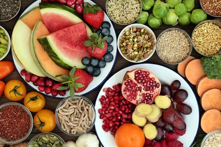 Concetto di cibo salutare con frutta fresca, verdura, semi, legumi, cereali e cereali con cibi ricchi di vitamine, minerali, antociani, antiossidanti e fibre, vista dall'alto. Archivio Fotografico