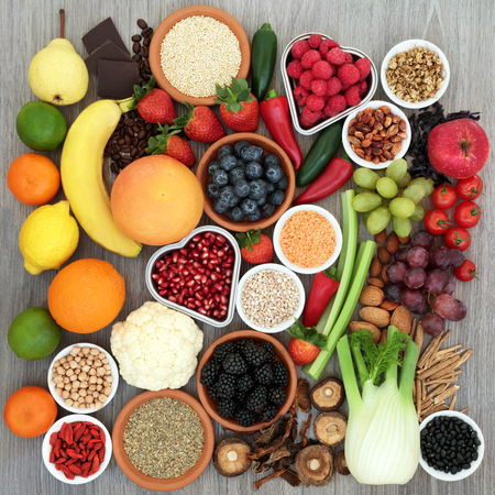 Diet health food concept with vegetables, fruit, pulses, grains, nuts, chocolate and herbs with tribulus terrestris used as an appetite suppressant. High in antioxidants, anthocyanins and fiber. Top view rustic style background.