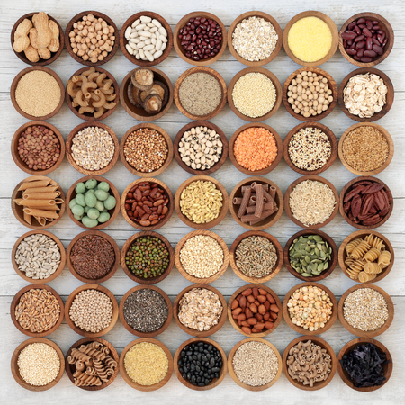 Dried macrobiotic super food with legumes, seeds, nuts, cereal, vegetables, grains and whole wheat pasta with foods high in protein, omega 3, anthocyanins, antioxidants, minerals and vitamins on rustic wood background, top view. Stock fotó
