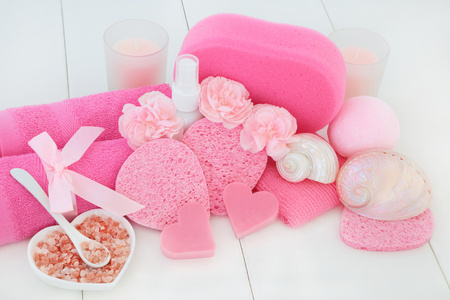 Spa and bathroom beauty treatment accessories with pink carnation flowers, himalayan ex foliating salt, heart shaped soaps, body lotion, sponges, wash cloths with seashells and pearls on white wood.