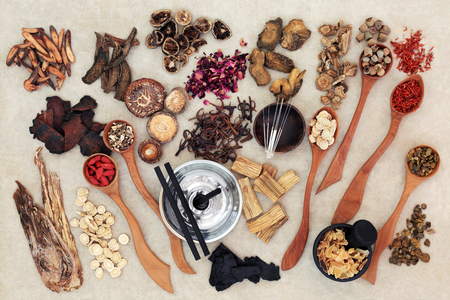 Chinese herbal medicine with traditional herbs, acupuncture needles, moxa sticks used in moxibustion therapy and mortar with pestle on hemp paper background. Top view. Stock Photo