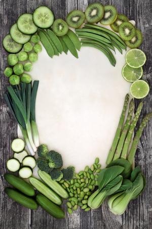 Green vegetable and fruit super food selection forming an abstract border on parchment paper and rustic wood background. Health food concept high in antioxidants, fiber, vitamins and minerals.