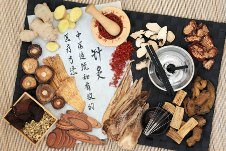 Chinese acupuncture needles and moxa sticks used in moxibustion therapy with herbs and calligraphy script on rice paper. Translation reads as acupuncture chinese traditional and effective medical treatment solution method. Top view.