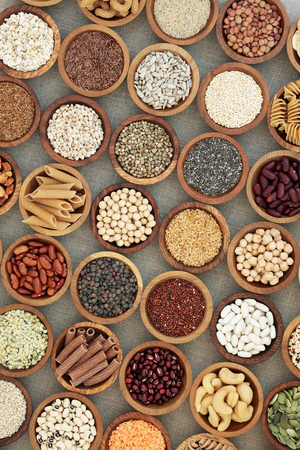 Vegan dried health food with nuts, seeds, legumes, pasta, grains and cereals. Food high in fiber, antioxidants, anthocyanins, vitamins and minerals. Top view on hessian background.