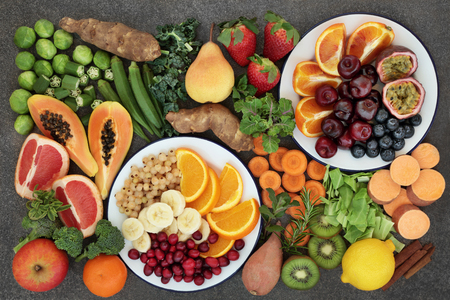 Health food concept for a high fiber diet with fresh fruit and vegetables very high in anthocyanins, antioxidants and vitamins on marble background top view.
