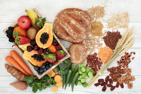 Gesundes ballaststoffreiches Diätlebensmittelkonzept mit Hülsenfrüchten, Obst, Gemüse, Vollkornbrot, Getreide, Körnern, Nüssen und Samen. Super Lebensmittel reich an Antioxidantien, Anthocyanen, Omega-3-Fettsäuren und Vitaminen. Rustikaler hölzerner Hintergrund, Draufsicht.