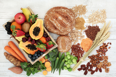 Healthy high fibre diet food concept with legumes, fruit, vegetables, wholegrain bread, cereals, grains, nuts and seeds. Super foods high in antioxidants, anthocyanins, omega 3 and vitamins. Rustic wood background, top view.