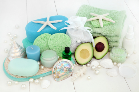 Avocado skincare and body care beauty treatment with bath salts, sponges, face cloths, aromatherapy essential oil, body lotion, facial cream, soap and decorative shells on white wood background.