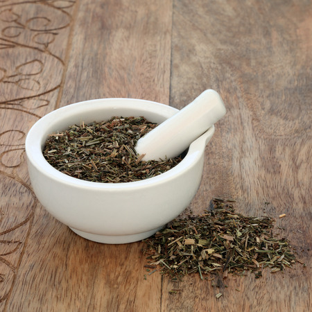 Cleavers leaf herb used in alternative herbal medicine to increase urinary flow and relieve fluid retention, heals skin conditions including psoriasis and has many other health benefits. In a mortar with pestle on rustic wood background. Galium aparine.