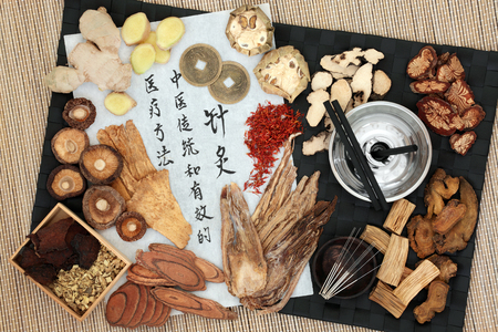 Chinese moxa sticks used in moxibustion therapy and acupuncture needles with herbs, feng shui coins and calligraphy script on rice paper. Translation reads as acupuncture chinese traditional and effective medical treatment solution method. Top view. Stock Photo