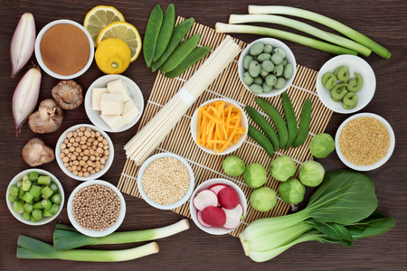 Macrobiotic diet food with japanese udon noodles, tofu, miso and wasabi paste, grains, legumes, vegetables and wasbai nuts with foods high in protein, antioxidants, fibe, vitamins and minerals. On bamboo and oak background, top view.