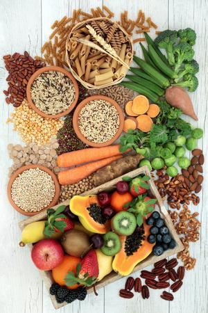 Alimentos saludables para una dieta alta en fibra con pastas integrales, granos, legumbres, nueces, frutas, verduras y cereales con alimentos ricos en ácidos grasos omega 3, antioxidantes y vitaminas. Vista superior de fondo rústico.