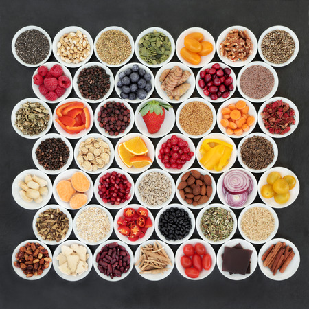 Health food for a healthy heart with chinese and ayurvedic herbal medicine, vegetables, fruit, nuts, seeds, pulses, cereals and grains and herbs on  slate. Very high in omega 3, antioxidants, anthocyanins, minerals and vitamins.