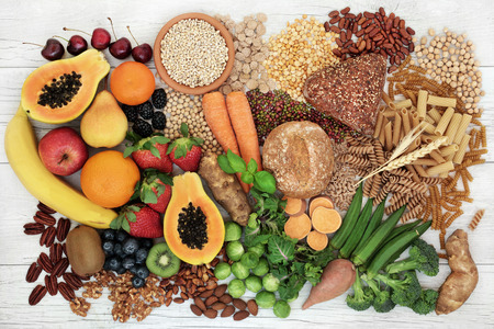 Food with high fiber content for a healthy diet with fruit, vegetables, whole wheat bread, pasta, nuts, legumes, grains and cereals. High in antioxidants, anthocyanins, vitamins and omega 3 fatty acid. Rustic background top view.