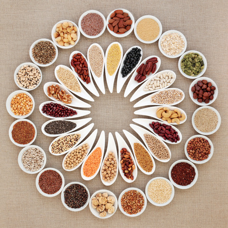 Vegan high protein dried super food selection with nuts, seeds, legumes and grains. Dried foods high in fiber, antioxidants, anthocyanins, minerals and vitamins. On hessian background, top view.