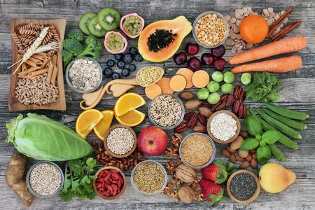 Concepto de alimentos saludables con alto contenido de fibra dietética con frutas, verduras, pasta de trigo integral, legumbres, cereales, nueces y semillas con alimentos ricos en omega 3, antioxidantes, antocianinas, carbohidratos inteligentes y vitaminas. Vista superior de fondo rústico.
