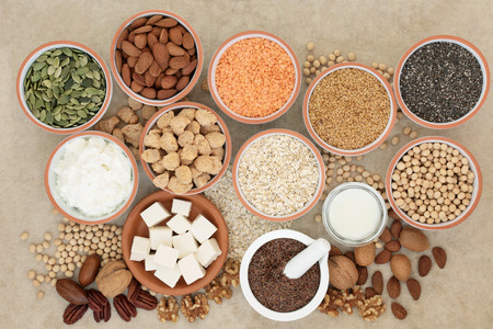 Vegan super food with tofu, seeds, nuts, legumes, soya milk, yoghurt and chunks. Foods high in fiber, antioxidants, vitamins and minerals. Top view on natural hemp paper background.