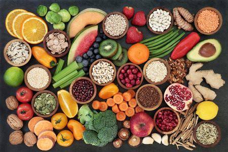Health food concept with fruit, vegetables, seeds, pulses, grains, cereals, herbs and spices with foods high in vitamins, minerals, anthocyanins, antioxidants and fiber on slate background top view.
