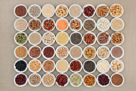 Vegan high protein dried superfood selection with nuts, seeds, legumes, cereals and grains. Health foods high in fiber, antioxidants, anthocyanins, minerals and vitamins. On hessian background, top view.