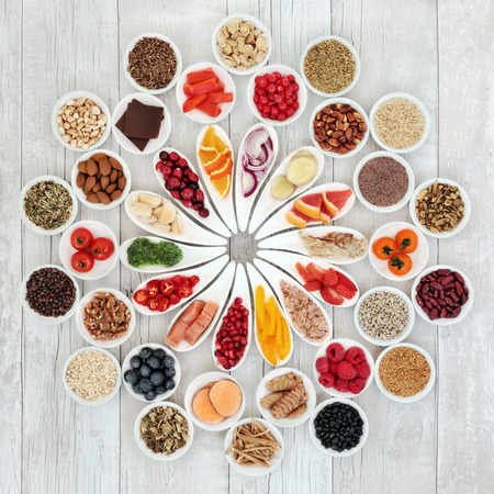 Super food for a healthy heart with fish, fruit, vegetables, grain, cereals, nuts, seeds and herbal medicine. Very high in omega 3, antioxidants, anthocyanins, smart carbohydrates, vitamins, and minerals. Stock Photo