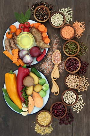 Health food concept with fresh vegetables, pulses, herbs, spice, himalayan salt and olive oil with foods high in vitamins, minerals, anthocyanins, antioxidants and fiber, top view on oak. Stock Photo