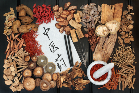 Chinese moxa sticks used in moxibustion therapy, acupuncture needles with traditional herbs, feng shui coins  and calligraphy script. Translation reads as chinese herbal medicine, Top view on dark oak.