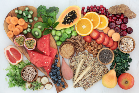 High fibre health food concept with multi seed crackers, cereals, nuts, fruit, vegetables and herbs. Foods high in omega 3 fatty acids, antioxidants, anthocynins and vitamins. Rustic background  top view.