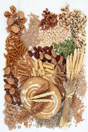 High fibre health food concept with fresh wholegrain rye bread, whole wheat pasta, nuts, cereals and grains, super foods high in omega 3, antioxidants and vitamins. Zdjęcie Seryjne