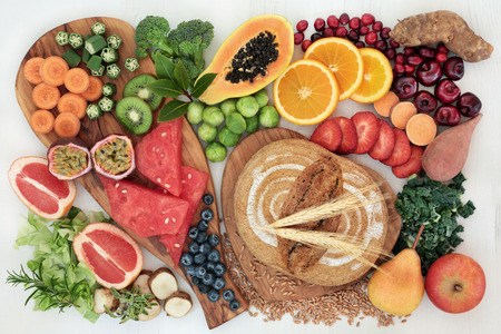 High dietary fiber super food concept with fresh fruit, vegetables, whole grain rye bread, herbs and spices top view on rustic background. Foods high in antioxidants, anthocyanins and vitamins.