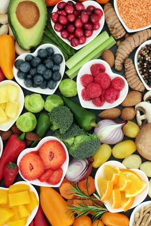 Healthy super food concept with fruit, vegetables, herbs spice and nuts in heart shaped dishes and loose. Foods high in antioxidants, omega 3 fatty acids, fibre,vitamins, minerals and anthocyanins. Stock Photo