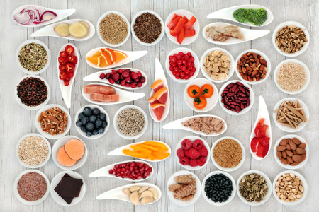 Health food for a healthy heart with fish, vegetables, fruit, nuts, seeds, pulses, spice and medicinal herbs. Super food concept. High in omega 3 fatty acid, smart carbohydrates, antioxidants, minerals and vitamins.