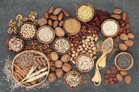 Food with high fibre content for a healthy diet with whole wheat bread, whole grain pasta, nuts, seeds, legumes, grains and cereals. High in antioxidants, anthocyanins, vitamins and omega 3 fatty acid. Marble background top view.