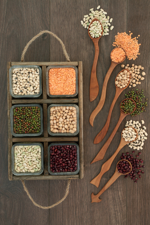 Dried pulses health food in wooden spoons and box on rustic oak background.