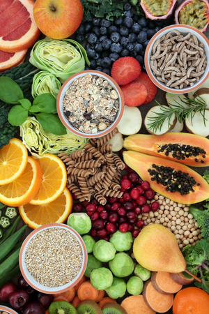 High fiber health food concept with cereals, whole wheat pasta, fruit, vegetables, legumes and cereals. Foods high in smart carbohydrates, antioxidants, anthocynins and vitamins. Top view.