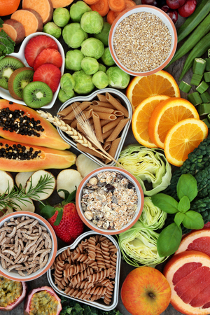 High dietary fiber health food concept with fresh fruit, vegetables, whole wheat pasta and cereals with foods high in antioxidants, anthocyanins, smart carbohydrates and vitamins. Top View. Stock Photo