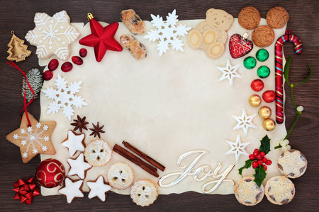 Christmas background border with joy sign including tree decorations, biscuits, cakes, chocolates and winter flora on parchment paper on rustic oak. Flat lay. Standard-Bild