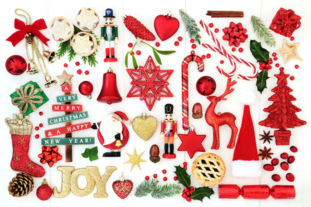 Christmas background with joy sign, retro and new tree bauble decorations, candy canes, mince pies, spices, winter flora, ribbons and bows on rustic white wood. Top view. Stock Photo