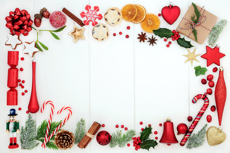 Christmas background border with traditional symbols of bauble decoration, mince pies, fruit, candy canes, spices, winter flora and gift box on rustic white wood.