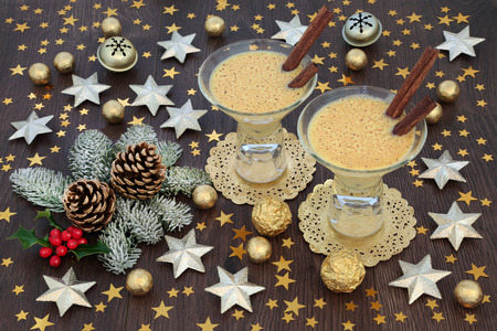 Christmas eggnog drink in glasses with gold star and bell decorations, foil wrapped chocolate balls with winter flora of holly, fir and pine cones on rustic oak table background. Festive theme.