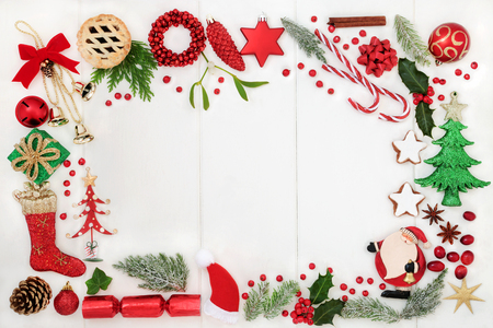 Christmas background border with traditional symbols of bauble decorations, candy canes, mince pies, fruit, spices and winter flora on rustic white wood. Top view. Stock Photo