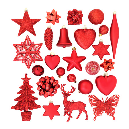 Red Christmas tree decorations, baubles, ornaments and symbols for the festive season on white background. Flat lay.