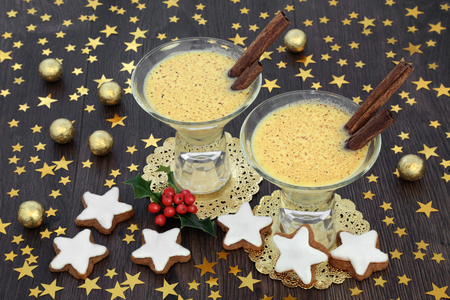 Traditional Christmas and winter eggnog drink for two with gingerbread cookies, gold star decorations, foil wrapped chocolate balls with holly on rustic oak background.