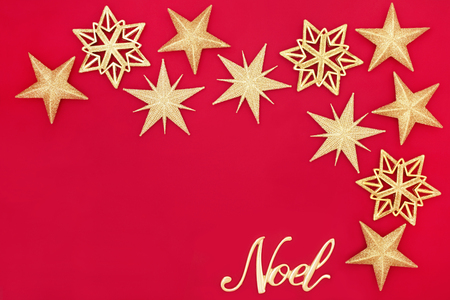 Christmas abstract background with glitter star bauble decorations and gold noel sign on red with copy space. Traditional Christmas greeting card for the festive season.