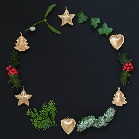 Abstract Christmas wreath garland with winter flora and bauble decorations on black background. Top view. Christmas card for the holiday season. Flat lay.