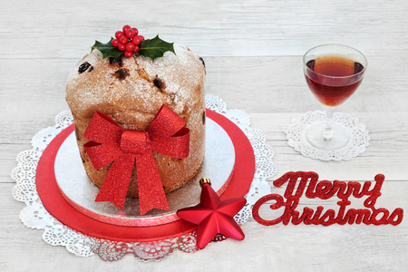 Panettone cake and alcoholic drink with merry christmas sign, red bauble decoration, bow and winter holly on rustic wood background. Traditional sweet bread, festive theme.
